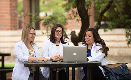 nursing students studying on bench outside