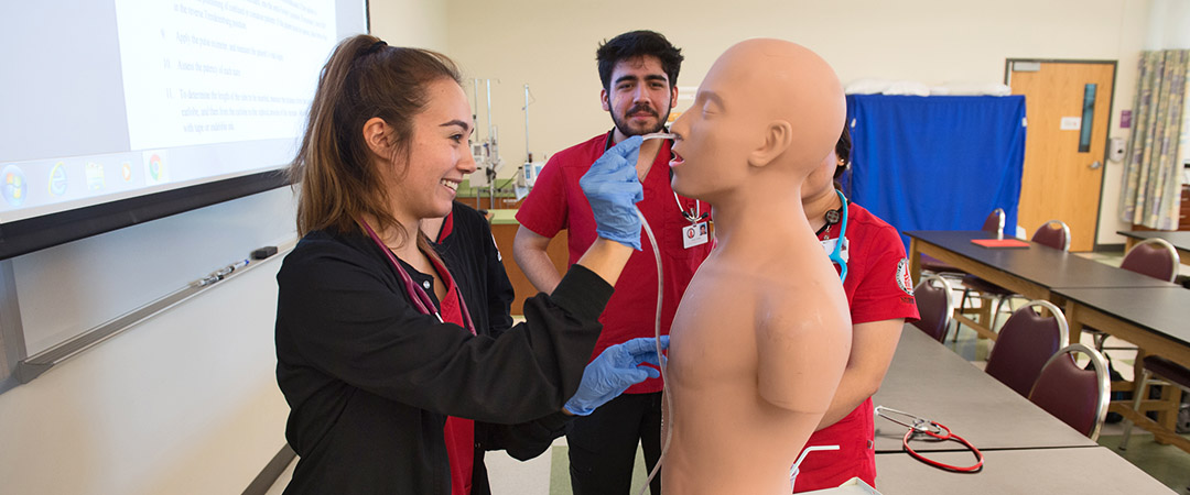 Nursing students practicing with mannequin